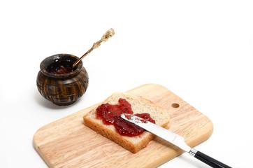 Marmeladenbrot auf Holzbrettchen und Marmeladenglas