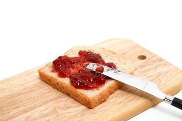 Marmeladenbrot auf Holzbrettchen und Messer