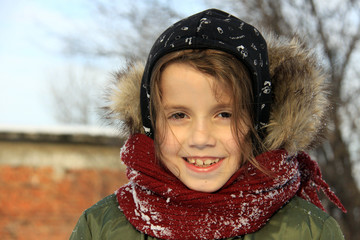 Little girl playing outdoors with snow