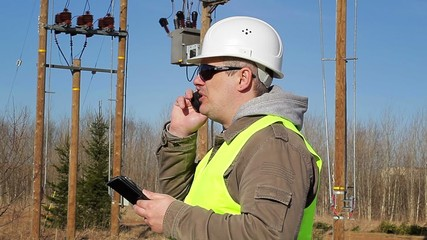 Electrical engineer with tablet PC talking on cell phone