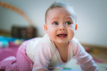 Adorable baby girl crawls on all fours floor at home. Crying