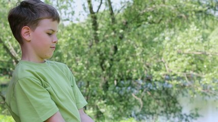 Boy in green t-shirt does exercises with dumbbell in park
