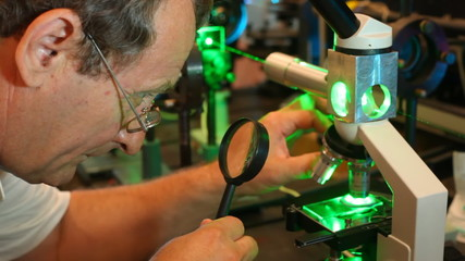man looks at microscope with green laser through magnifying glass close up