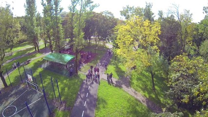 Many children in park looking at flying camera, shaky image