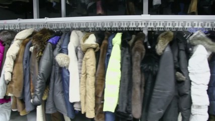 Many winter clothes hang at conveyor which moves