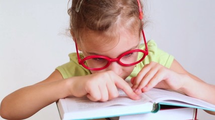 little girl in red glasses reads a book and leads look