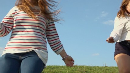 Two young girls hold hands and run closer by grass hill at sunny summer day