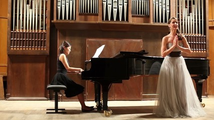 Woman pianist plays the piano and elegance singer sing opera song