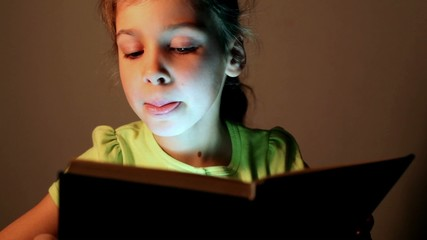 little girl in blouse attentively reads aloud book dark room