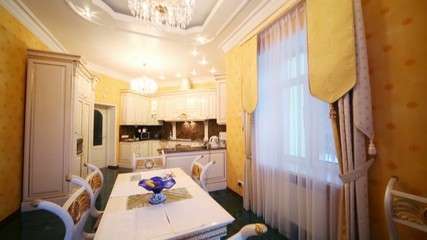 Kitchen with furniture in classic style and dining table