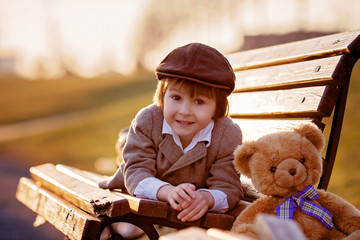Adorable little boy with his teddy bear friend in the park