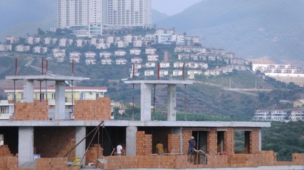 Workers erect balconies from brick in new building against beautiful many-storeyed house, time lapse