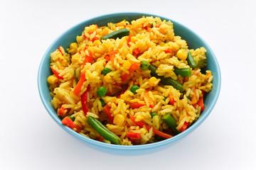 Рис с овощами в голубой миске на белом фоне