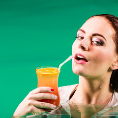 Woman drinking tropical drink in water.