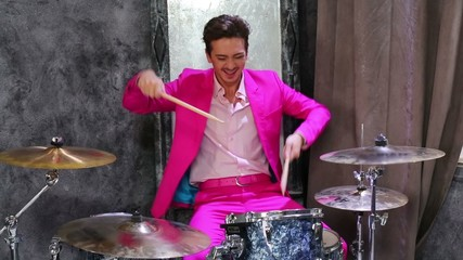Young man in pink suit play on drum-set at dark room