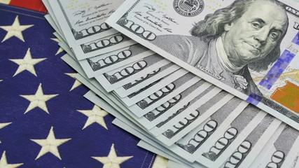 Pile of hundred dollar bills on American flag in 4K UHD video.
