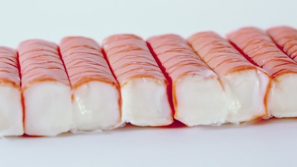 Row of eight red crab sticks spin isolated on white background