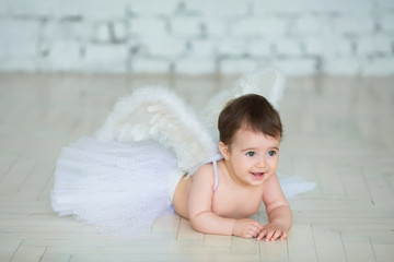 Portrait of cute little baby with angel wings smiling