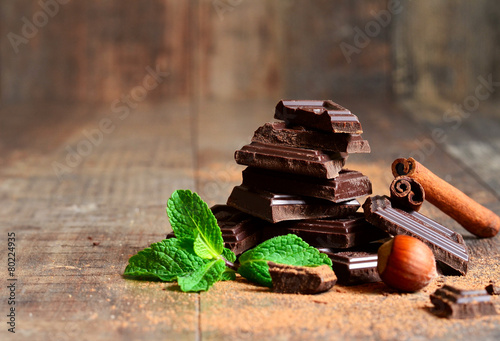Stack of chocolate slices with mint leaf,hazelnut and cinnamon. - 80224935