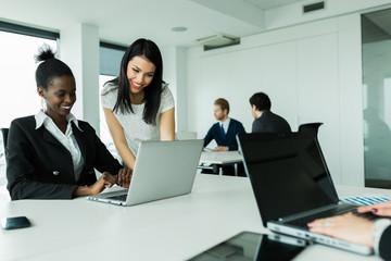 Women working on laptops in an office