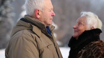 Happy elderly husband and wife smile and caress in park