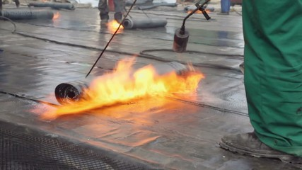 Labourers use burners to warm ruberoid for waterproofing