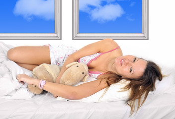 sexy girl in nightgown on bed  hugging teddy bear smiling happy