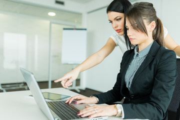 Businesswomen looking and pointing at a laptop
