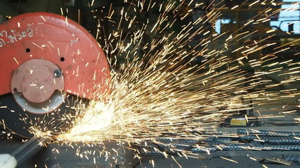 Slow motion metal saw cutting a steel, spark lighting.