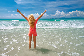 Happy young woman standing on the beach and looking at sea