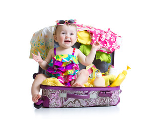 Baby girl sitting in trunk with things for vacation travel