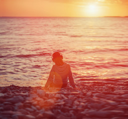 Girl in headphones sitting on beach at sunset