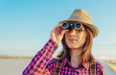 Traveler young woman looking through binoculars