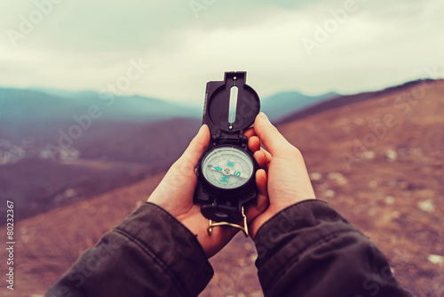Hiker woman with a compass in the mountains
