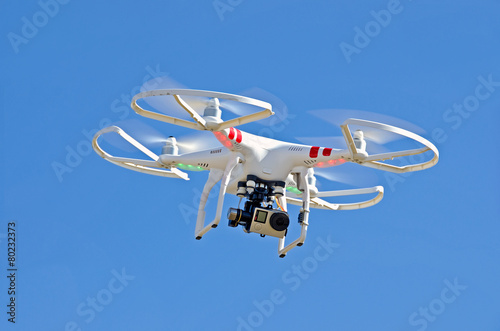 Juliste white drone hovering in blue sky