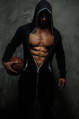 Male in a hood with basket ball