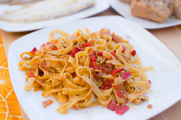 Pasta with meat on white plate.