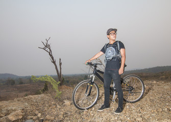 Young man and bicycle on moutain