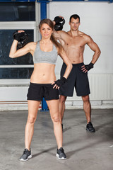 man and woman lifting kettle bell crossfit