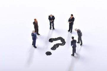 クエスチョンマークを囲んで会議をしているビジネスマン