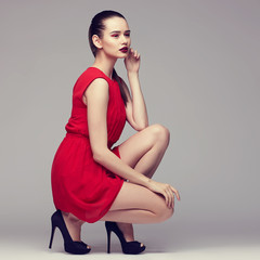 young elegant woman in red dress, fashion studio shot