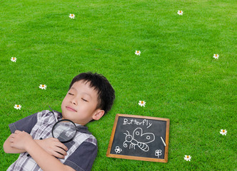 Sleeping Asian boy with magnifying glass in grass field
