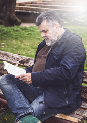 Attractive bearded man reading in a park