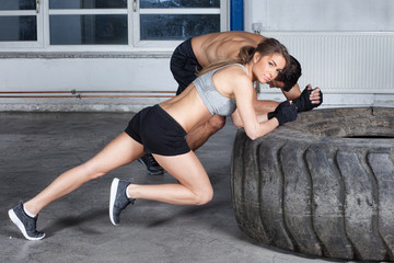 man and woman on a tire crossfit fitness training warm up