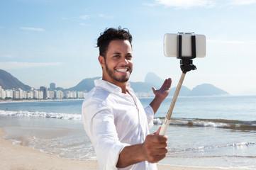 Fröhlicher Brasilianer an der Copacabana mit Selfie-Stick
