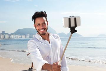 Lachender Brasilianer an der Copacabana mit Selfie-Stick