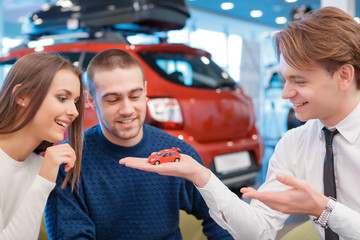 Salesman demonstrates toy car model to customers