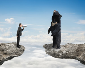 Businessman yelling at black bear on cliff with sky cloudscape