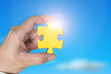 Hand holding gold jigsaw puzzle piece with blue sky sunlight