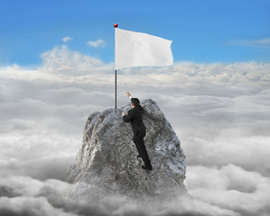 Businessman hand wanting for white flag on peak with cloudscape